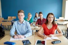 Estudiantes con los cuadernos y PC de la tableta en la escuela Fotografía de archivo libre de regalías