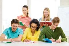Estudiantes con los libros de texto y los libros en la escuela Foto de archivo libre de regalías