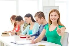 Estudiantes con los libros de texto y los libros en la escuela Imagen de archivo
