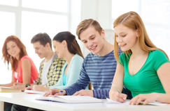 Estudiantes con los libros de texto y los libros en la escuela Imagen de archivo libre de regalías