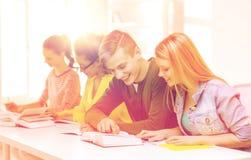Estudiantes con los libros de texto y los libros en la escuela Fotografía de archivo libre de regalías