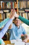 Estudiantes con los libros que hacen el alto cinco en biblioteca Foto de archivo libre de regalías