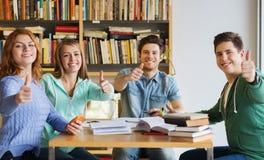 Estudiantes con los libros que muestran los pulgares para arriba en biblioteca Fotografía de archivo libre de regalías