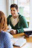 Estudiantes con los libros que se preparan al examen en biblioteca Imagen de archivo