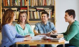 Estudiantes con los libros que se preparan al examen en biblioteca Imágenes de archivo libres de regalías