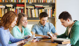 Estudiantes con los libros que se preparan al examen en biblioteca Imagen de archivo libre de regalías