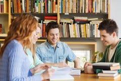 Estudiantes con los libros que se preparan al examen en biblioteca Foto de archivo libre de regalías