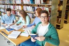 Estudiantes con los libros que se preparan al examen en biblioteca Foto de archivo