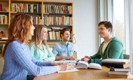 Estudiantes con los libros que se preparan al examen en biblioteca Fotos de archivo libres de regalías