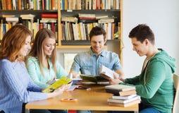 Estudiantes con los libros que se preparan al examen en biblioteca Fotografía de archivo libre de regalías