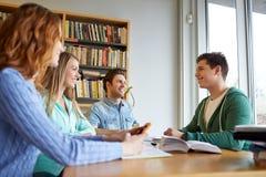 Estudiantes con los libros que se preparan al examen en biblioteca Fotos de archivo