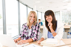 Estudiantes con los libros y la computadora portátil en sala de clase Foto de archivo