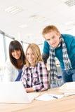 Estudiantes con los libros y la computadora portátil en sala de clase Foto de archivo libre de regalías