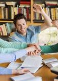 Estudiantes con los libros y las manos en el top en biblioteca Fotografía de archivo libre de regalías