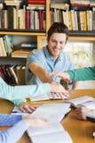 Estudiantes con los libros y las manos en el top en biblioteca Imagen de archivo libre de regalías