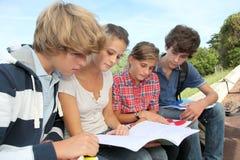 Estudiantes con los manuales en yarda de escuela imágenes de archivo libres de regalías