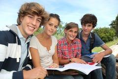 Estudiantes con los manuales en yarda de escuela Imagen de archivo