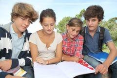 Estudiantes con los manuales en yarda de escuela Imagenes de archivo