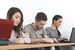Estudiantes con los ordenadores portátiles y las tabletas Fotos de archivo libres de regalías