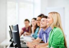 Estudiantes con los ordenadores que estudian en la escuela Fotos de archivo