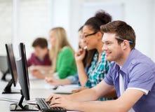 Estudiantes con los ordenadores que estudian en la escuela Imagen de archivo