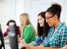 Estudiantes con los ordenadores que estudian en la escuela Fotos de archivo libres de regalías