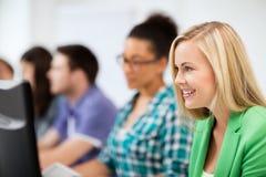 Estudiantes con los ordenadores que estudian en la escuela Imagen de archivo libre de regalías