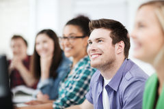 Estudiantes con los ordenadores que estudian en la escuela Imágenes de archivo libres de regalías