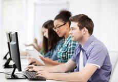 Estudiantes con los ordenadores que estudian en la escuela Fotografía de archivo libre de regalías