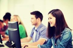 Estudiantes con los ordenadores que estudian en la escuela Foto de archivo libre de regalías