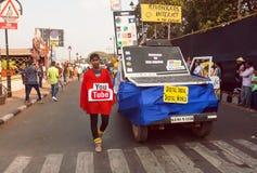 Estudiantes con los símbolos del web de Internet que caminan más allá de la calle durante el carnaval tradicional de Goa Foto de archivo libre de regalías