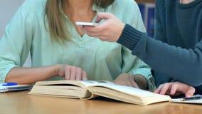 Estudiantes con los smartphones que toman la imagen de la página de los libros y que hacen la chuleta en biblioteca escolar Fotografía de archivo