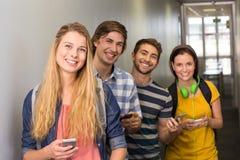 Estudiantes con los teléfonos móviles en el pasillo de la universidad Foto de archivo