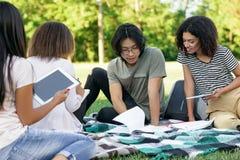 Estudiantes concentrados jóvenes que estudian al aire libre Fotos de archivo libres de regalías
