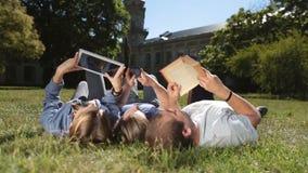Estudiantes concentrados que aprenden junto en hierba almacen de metraje de vídeo