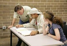 Estudiantes de ayuda del profesor Imagen de archivo libre de regalías
