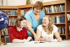 Estudiantes de ayuda del profesor cómodo Foto de archivo