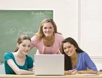 Estudiantes de ayuda del profesor en la computadora portátil Fotografía de archivo libre de regalías