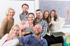 Estudiantes de diversa edad que hacen el selfie del grupo en smartphone Foto de archivo
