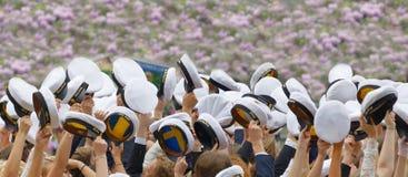 Estudiantes de graduación suecos felices en un parque hermoso con la lila Imagen de archivo