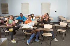 Estudiantes de Highschool que ensucian en clase durante rotura Foto de archivo libre de regalías