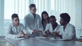 Estudiantes de la diversidad con la tableta que estudian el estetoscopio almacen de video