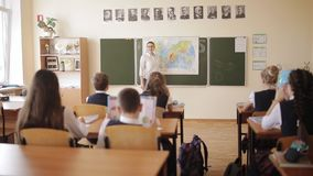 Estudiantes de la escuela secundaria con el uniforme escolar que se sienta en la sala de clase y atento que escucha una conferenc almacen de video