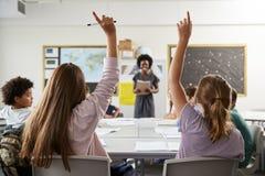 Estudiantes de la escuela secundaria que aumentan las manos para contestar a la pregunta fijada por el profesor In Classroom foto de archivo