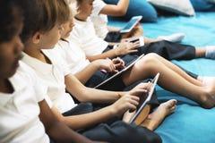 Estudiantes de la guardería que usan los dispositivos digitales imagen de archivo libre de regalías