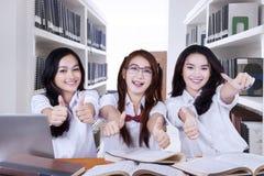Estudiantes de la High School bastante secundaria que dan los pulgares para arriba Imagen de archivo
