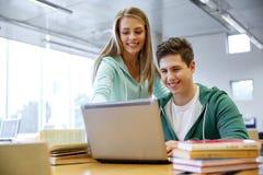 Estudiantes de la High School secundaria con el ordenador portátil en sala de clase Fotografía de archivo libre de regalías