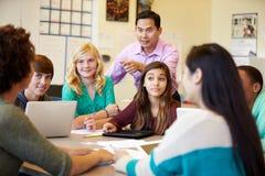 Estudiantes de la High School secundaria con los ordenadores portátiles de In Class Using del profesor Imagen de archivo