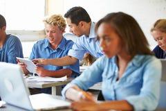 Estudiantes de la High School secundaria con los ordenadores portátiles y las tabletas de Digitaces fotografía de archivo libre de regalías