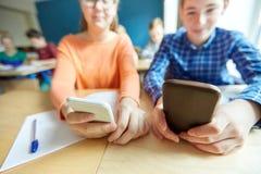 Estudiantes de la High School secundaria con mandar un SMS de los smartphones Foto de archivo